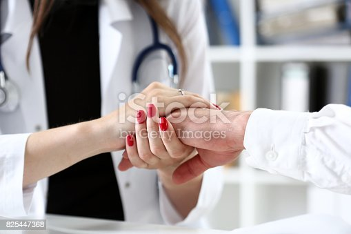 1133353454istockphoto Friendly female doctor hold patient hand in office 825447368