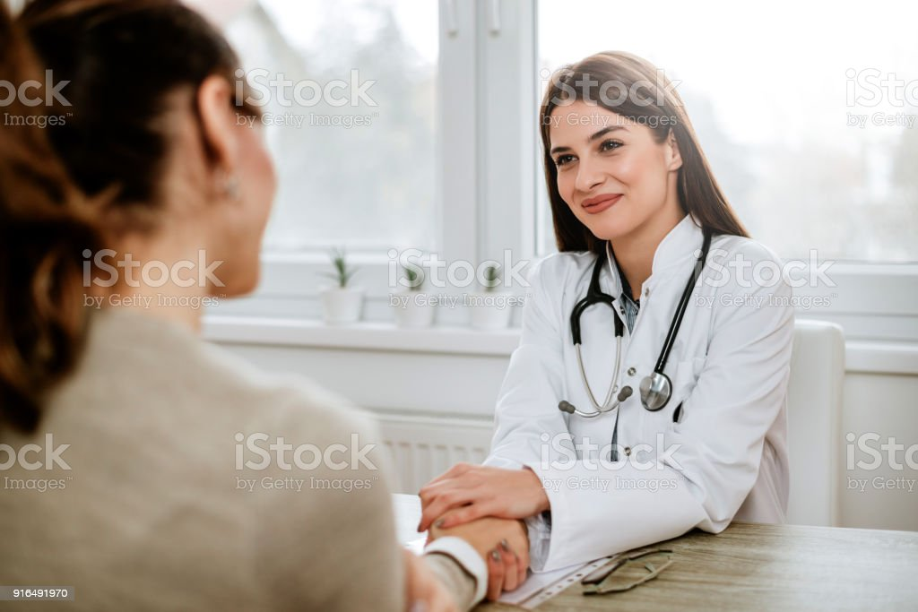 Friendly female doctor holding female patient's hand for encouragement and empathy. stock photo