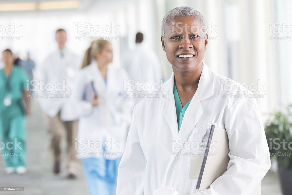 Friendly female doctor smiling in crowded hospital stock photo