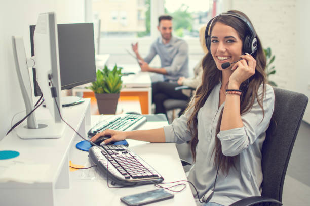 Friendly female helpline operator in call center. Saleswoman in headset using computer in office. stock photo