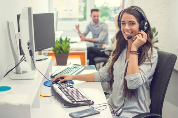 Freundlicher weiblicher Helpline-Betreiber im Callcenter. Verkäuferin im Headset mit Computer im Büro. – Foto
