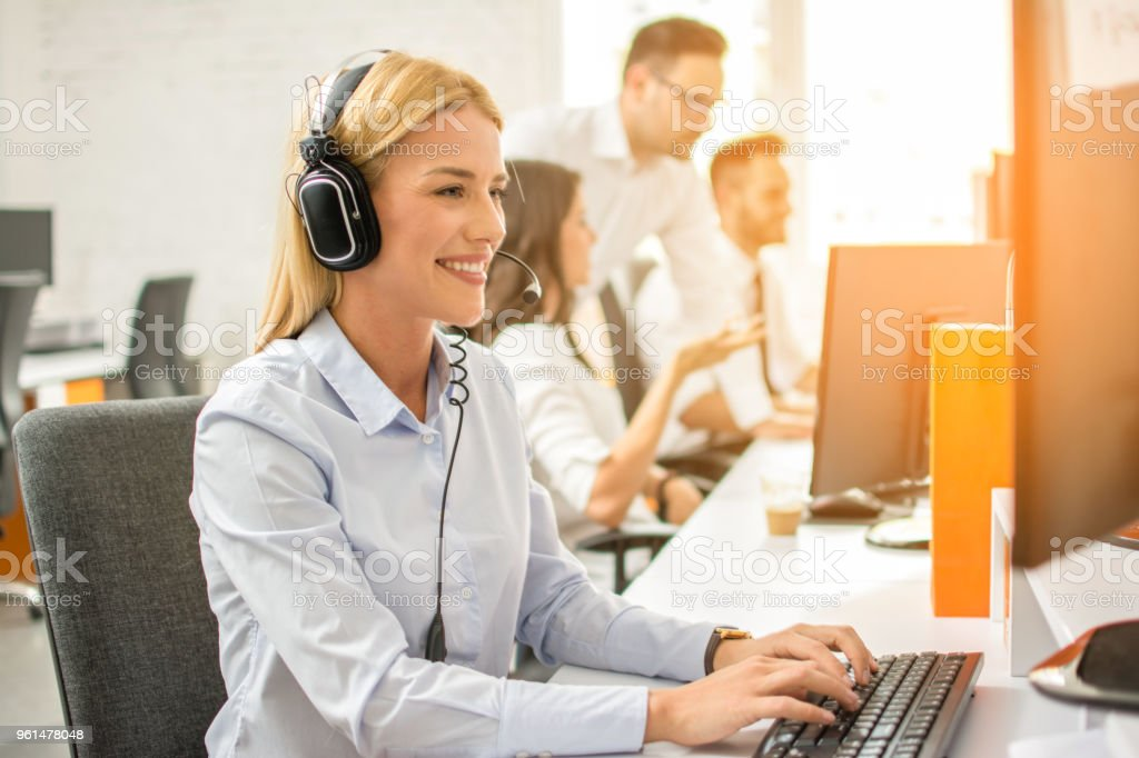 Friendly female helpline operator with headphones working on computer in office stock photo