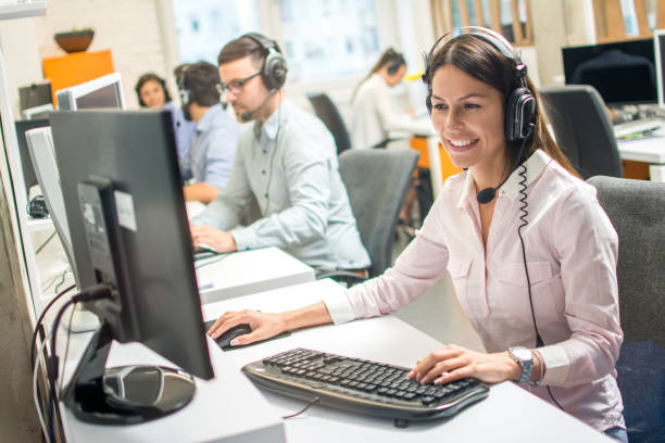 Friendly female operator consulting client on hotline in call center stock photo