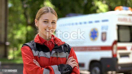 istock Friendly female paramedic posing for camera, ambulance on background, save lives 1131889453