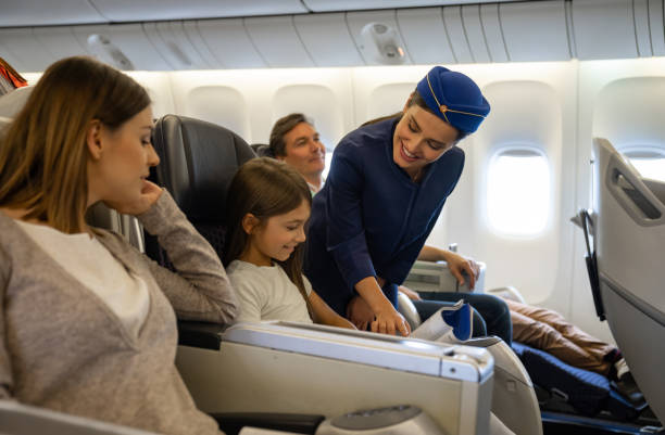 Friendly flight attendant helping a girl in an airplane Portrait of a friendly flight attendant helping a girl in an airplane and looking very happy - travel concepts air stewardess stock pictures, royalty-free photos & images