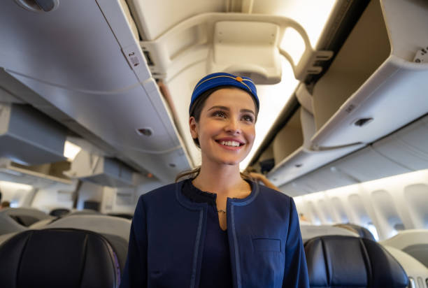 Friendly flight attendant smiling on the aisle in an airplane Portrait of a friendly flight attendant smiling on the aisle in an airplane and smiling - travel concepts cabin crew stock pictures, royalty-free photos & images