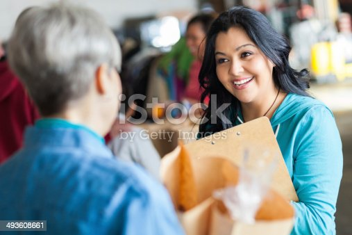 623523102 istock photo Friendly food bank volunteer accepting grocery donations from senior 493608661
