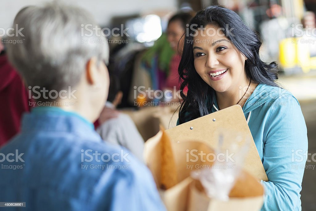 Friendly food bank volunteer accepting grocery donations from senior stock photo