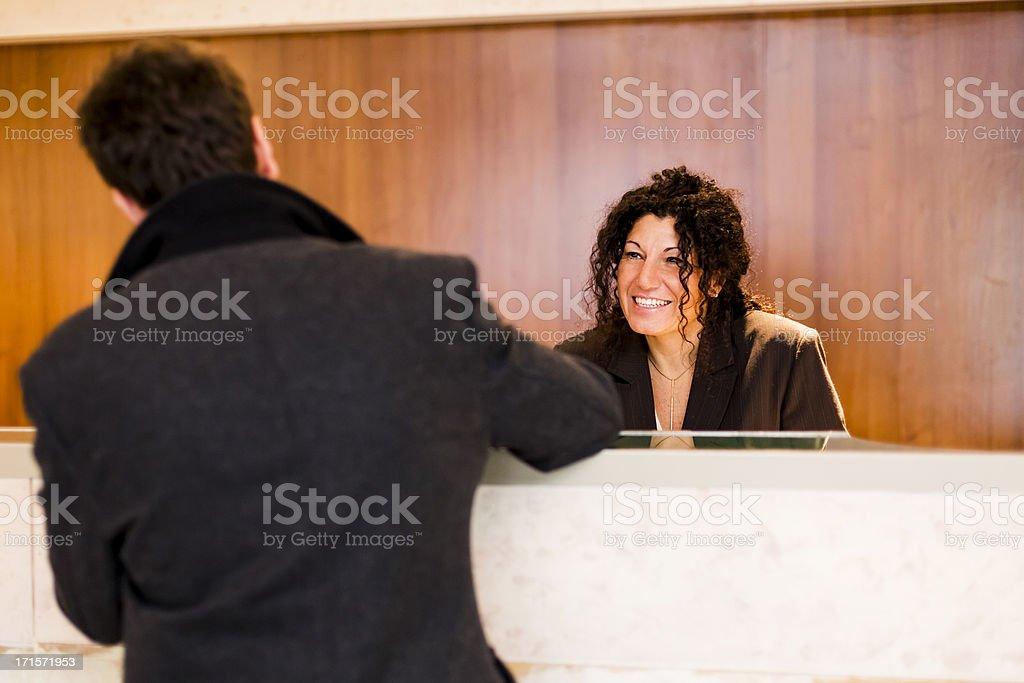 Balcão de recepção simpático trabalhador ajudar o hóspede check-in no hotel - foto de acervo