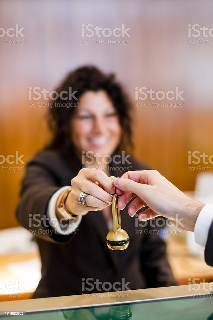 Friendly front desk worker helping guest check into hotel royalty-free stock photo