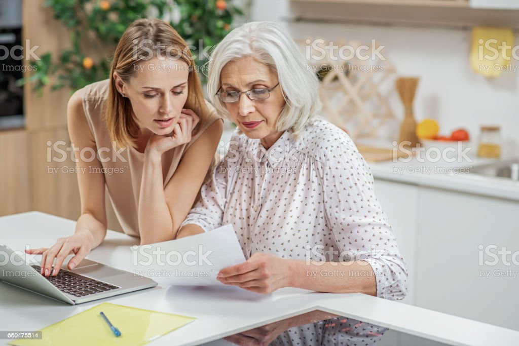 Friendly girl explaining some documentation to parent stock photo