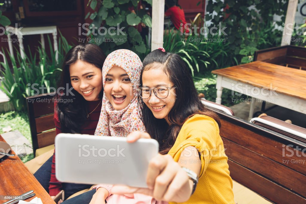 Friendly girls making selfie in cafe stock photo