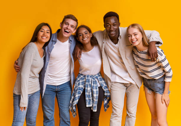 Friendly group of international students smiling over yellow background Friendly group of multiethnic students embracing and smiling over yellow background teenagers stock pictures, royalty-free photos & images