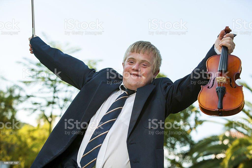 Friendly handicapped boy raising violin outdoors. royalty-free stock photo