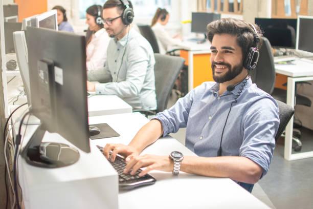 Freundlicher stattliche junge Mann mit Freisprech-Headset arbeiten am Computer in Call-Center – Foto