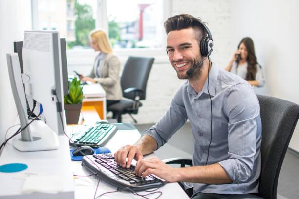 Freundlicher junger Mann mit Headset, der am Computer im Büro arbeitet – Foto