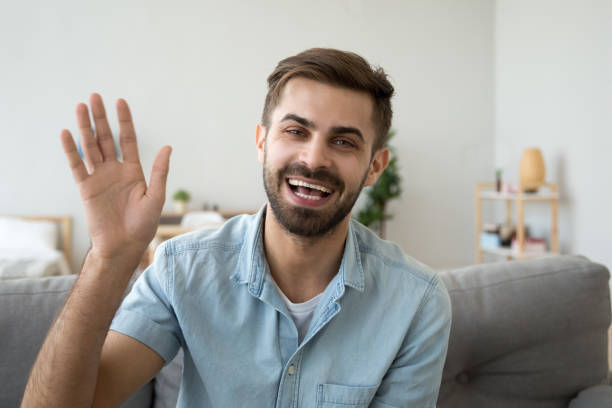 friendly happy man waving hand saying hello looking at camera - webcam stock pictures, royalty-free photos & images