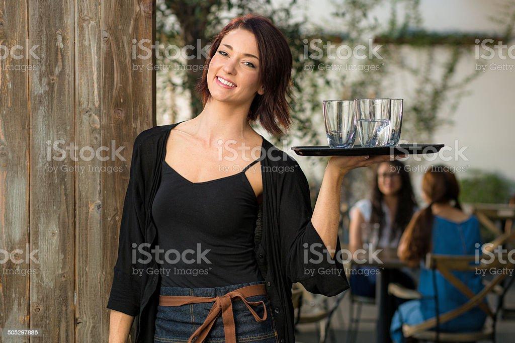 Friendly happy young female waiter server restaurant establishment patio outdoor stock photo