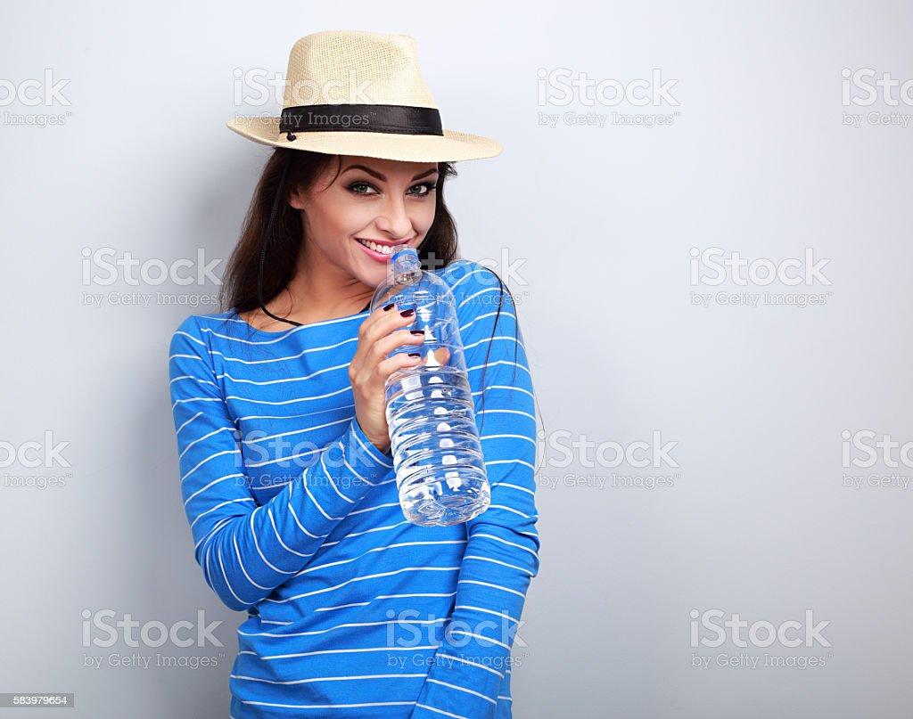 Friendly healthy woman in summer hat drinking still water stock photo