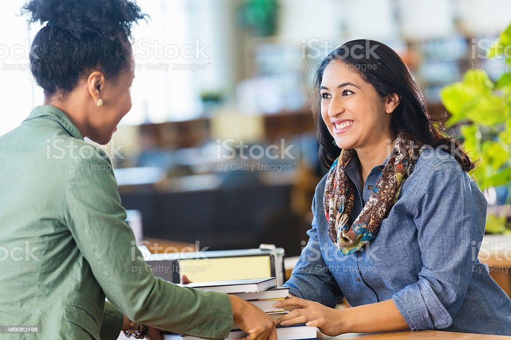 Friendly Hispanic librarian is assisting adult student in college library stock photo