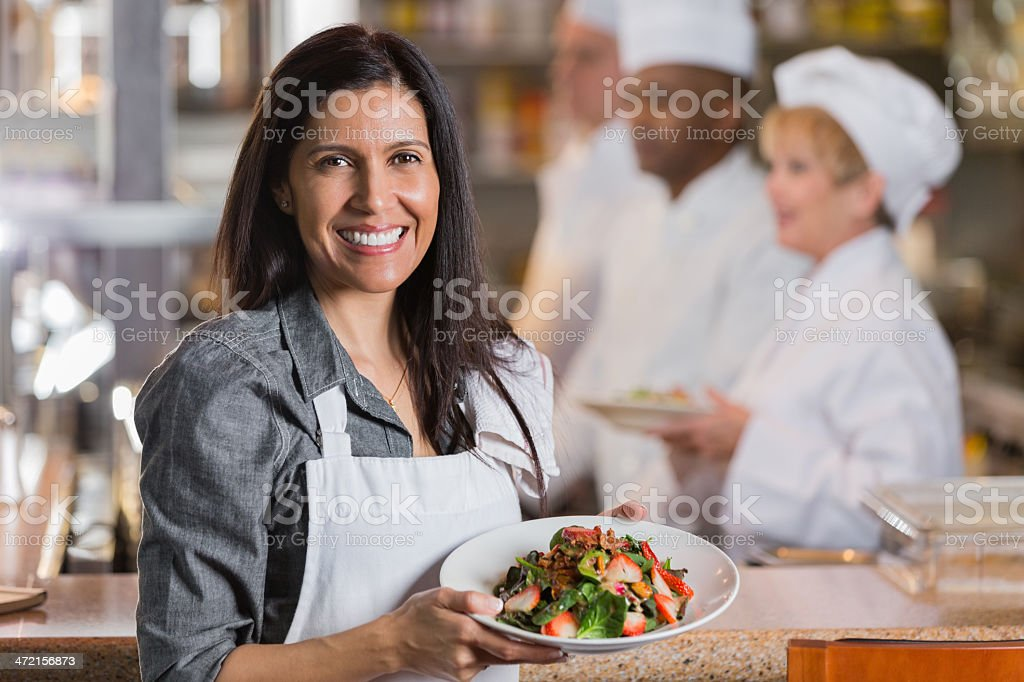 Friendly Hispanic waitress delivering customer's food from restaurant kitchen royalty-free stock photo