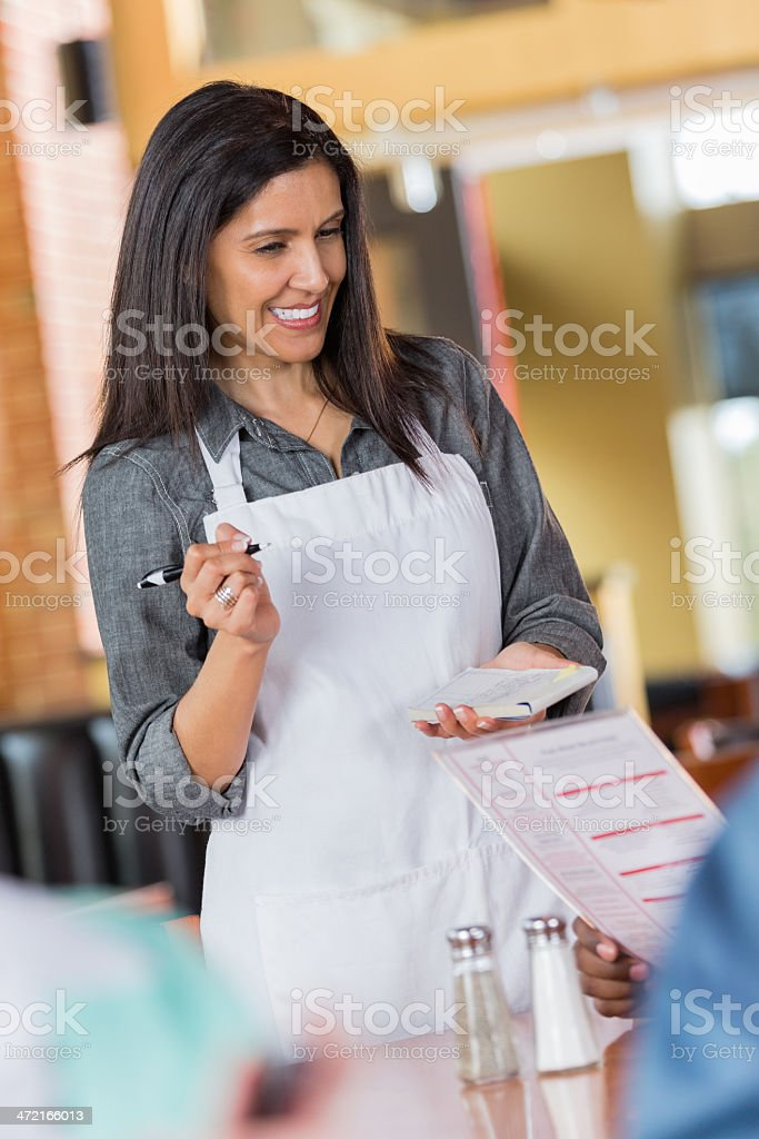 Friendly Hispanic waitress taking food order from restaurant customers royalty-free stock photo