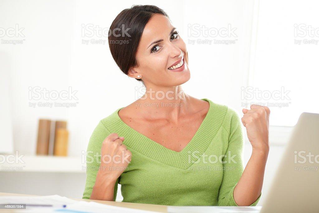 Friendly hispanic woman celebrating a success royalty-free stock photo