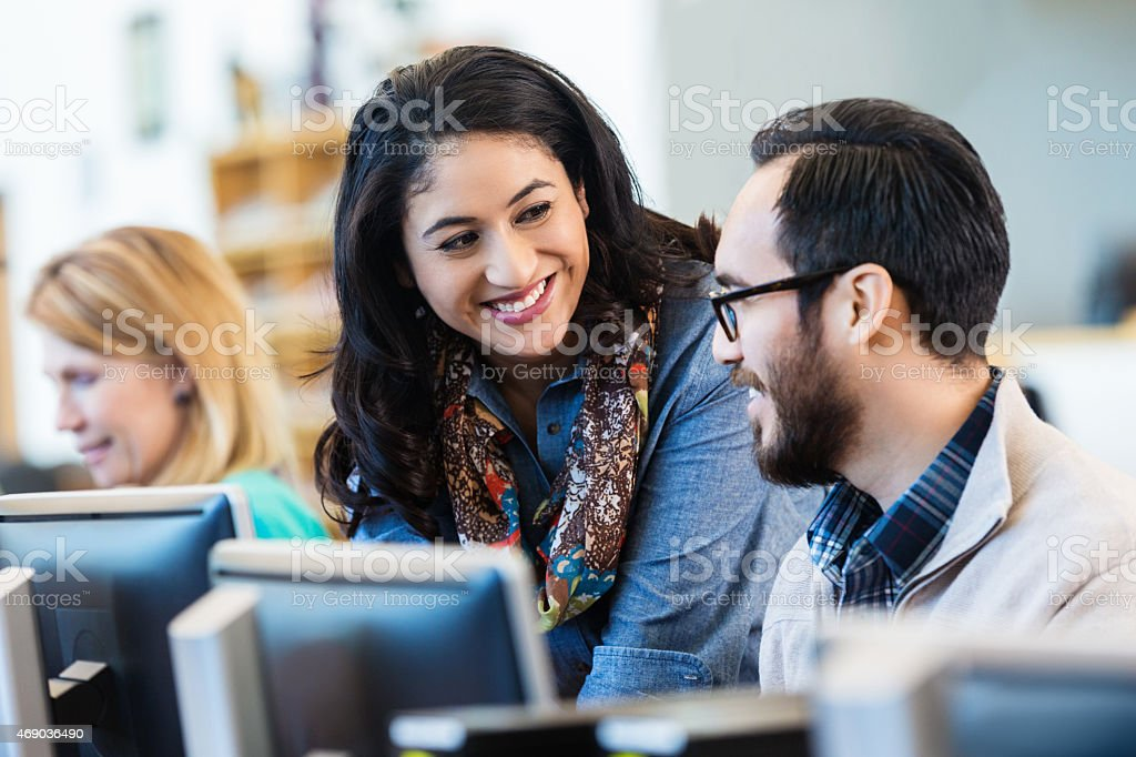 Friendly Hispanic woman talking with college classmate stock photo