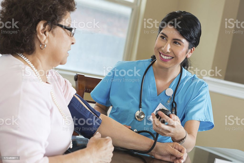 Friendly home healthcare nurse caring for senior patient royalty-free stock photo