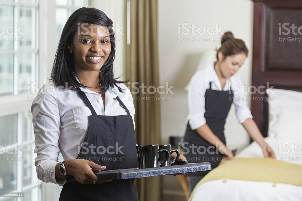 Friendly hotel maid delivering room service