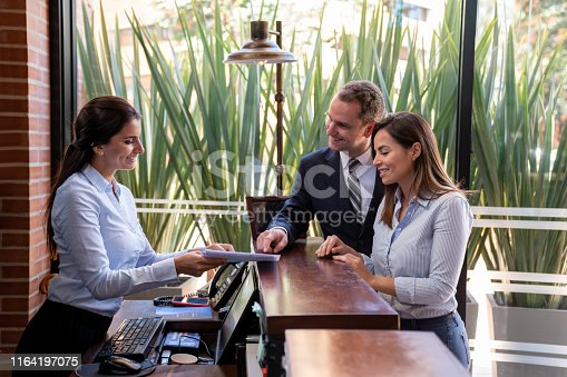istock Friendly hotel receptionist handing a form to fill in to customer business couple 1164197075