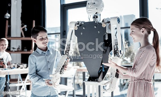 istock Friendly kids discussing human like robot 939690736
