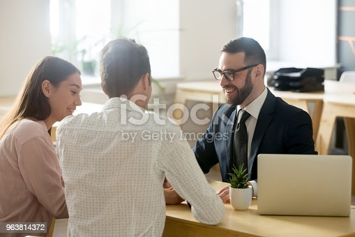 istock Friendly lawyer or financial advisor in suit consulting young couple 963814372