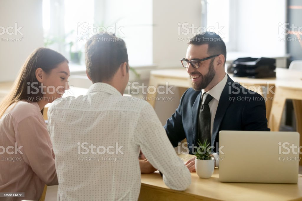 Friendly lawyer or financial advisor in suit consulting young couple stock photo