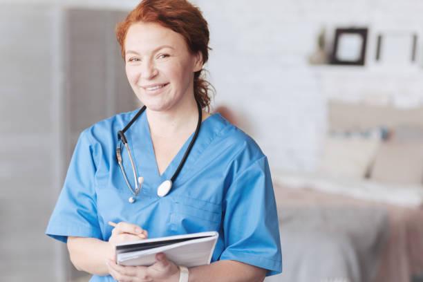 vänliga söker sjuksköterska med bärbar dator leende in kameran - andningssystem bildbanksfoton och bilder