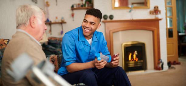 vriendelijke mannelijke zorg verpleegkundige - thuiszorg stockfoto's en -beelden