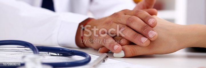 1021670950istockphoto Friendly male doctor hold female arm in office 1070900010