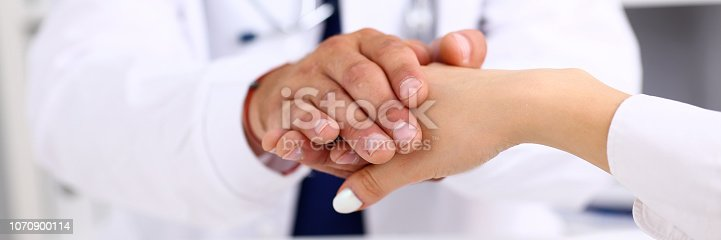 1021670950istockphoto Friendly male doctor hold female arm in office 1070900114