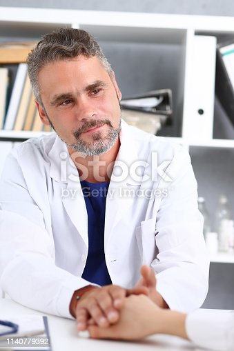 1133353454istockphoto Friendly male doctor hold female arm in office 1140779392