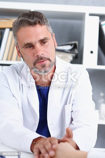 1133353454istockphoto Friendly male doctor hold female arm 940905380