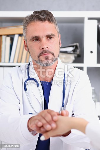 1133353454istockphoto Friendly male doctor hold female arm 940905386