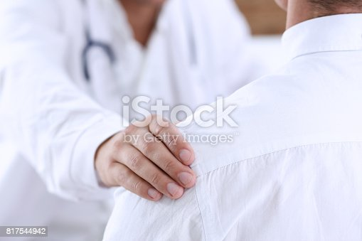 1133353454istockphoto Friendly male doctor hold patient shoulder in office during reception 817544942