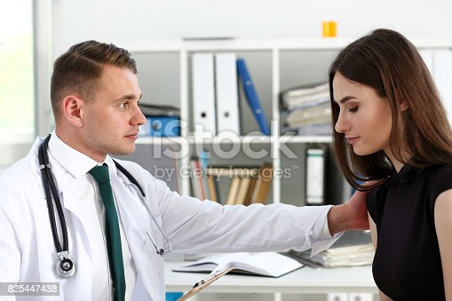 1133353454istockphoto Friendly male doctor hold patient shoulder in office 825447438