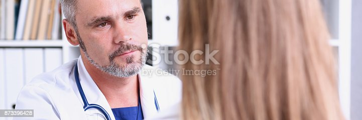 1133353454istockphoto Friendly male doctor hold patient shoulder in office 873396428