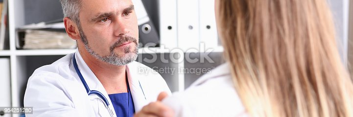 1133353454istockphoto Friendly male doctor hold patient shoulder 954251280
