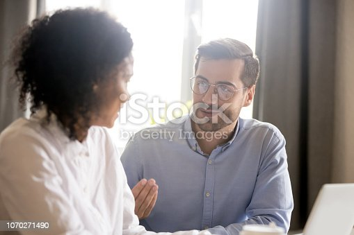 Friendly male mentor teacher training employee explaining african-american female intern student teaching new project, diverse colleagues talking in office, working together, help coaching concept
