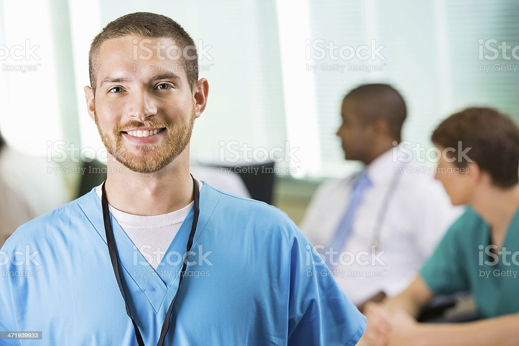 Friendly male nurse or physician in hospital staff meeting stock photo
