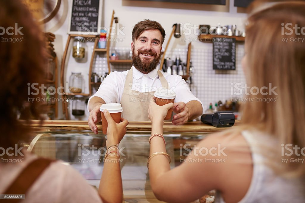 Friendly man serving coffee for two women stock photo