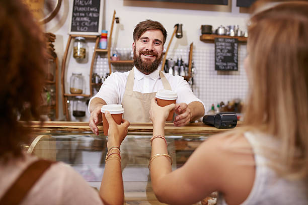 friendly man serving coffee for two women - barista stock photos and pictures