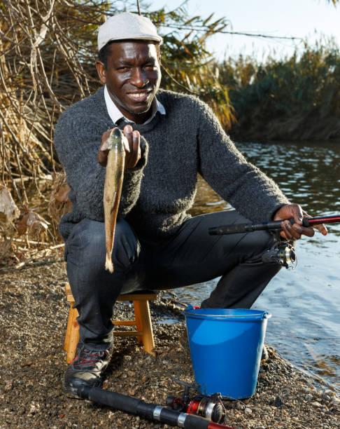 friendly mature afro fisherman - fishman imagens e fotografias de stock